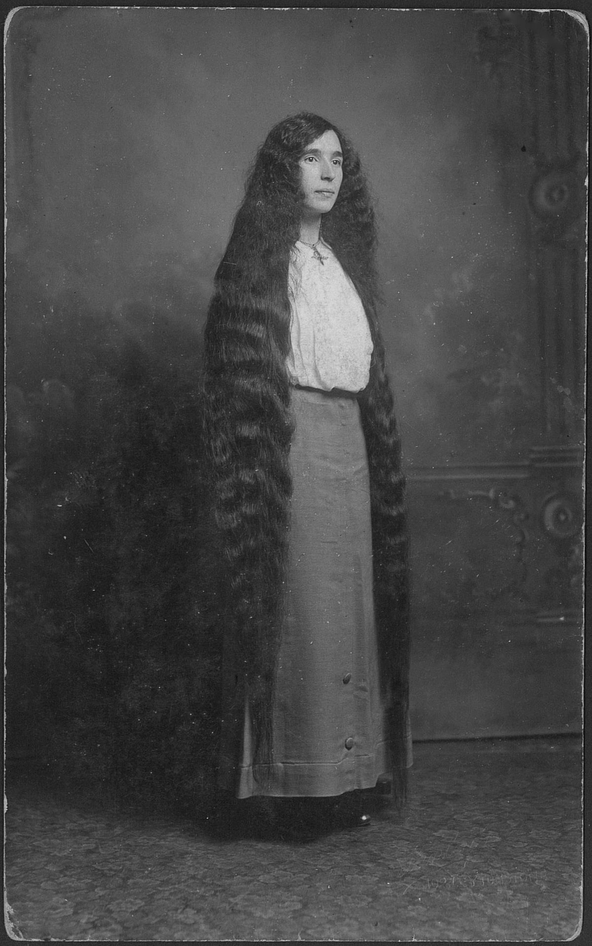 Portrait of a young woman with long hair almost to the floor, circa 1900s