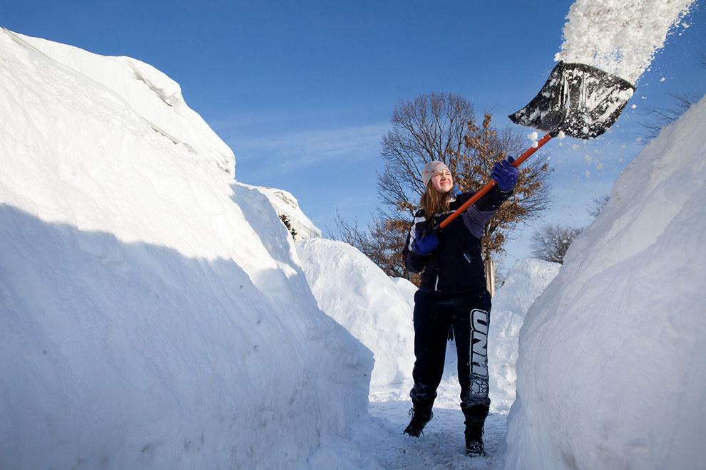 девушка чистит снег лопатой