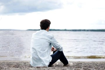 мужчина на берегу моря смотрит вдаль и думает